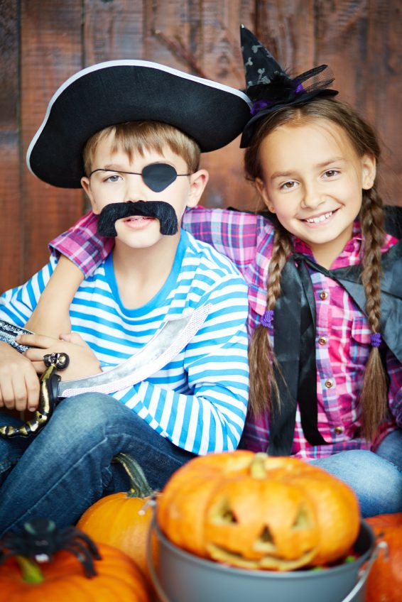 little children in Halloween costumes of pirate and witch