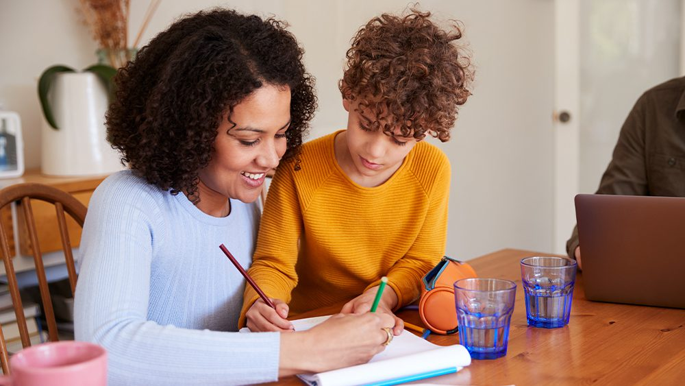 Mother Helping Son With Homework On KitchenTable